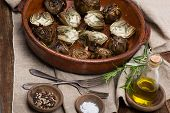 image of artichoke hearts  - Artichoke hearts on big dish served with olive oil pepper and salt on the wooden table - JPG