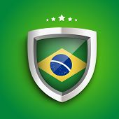 Stylish glossy winners shield with brazil flag inside on green background.