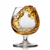 Splash of cognac in glass isolated on white background