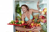 Woman sitting in a fridge in the lotus position surrounded by fruits holding a cutting board with cu