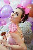 Cute young woman posing with pink lollipop