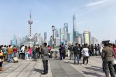 SHANGHAI, CHINA - APRIL 7, 2014: People on The Bund waterfront in Shanghai