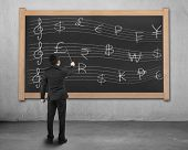 Businessman Conducting With Money Symbols Stave On Blackboard