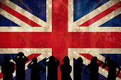 Silhouettes of football supporters against union jack flag in grunge effect