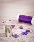 Antique silver thimble with threaded needle and purple buttons