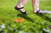 Woman wearing spiked lawn revitalizing aerating shoes, gardening concept