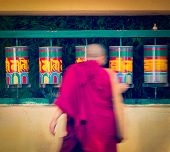 Vintage retro effect filtered hipster style travel image of Buddhist monk passing and rotating praye
