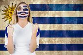 Excited fan in uruguay face paint cheering against uruguay flag in grunge effect