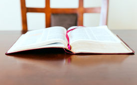 picture of godly  - Open Bible over a desk or table. Open word of God waiting for the pastor or believer. The need of coming back to the word of God as source of guidance. ** Note: Shallow depth of field - JPG