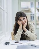 Portrait of bored businesswoman sitting at desk in office