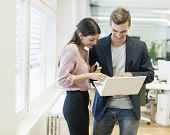 Young businessman and businesswoman using laptop in office