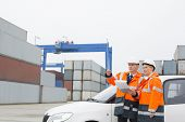 Workers examining cargo in shipping yard