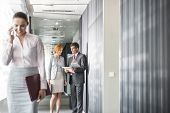 Business people discussing in corridor with colleague using cell phone in foreground