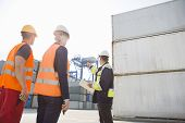 Male supervisor discussing with workers in shipping yard