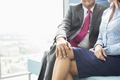 Midsection of businessman flirting with female colleague in office