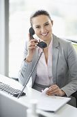 Smiling young businesswoman talking on telephone in office