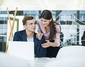 Young businessman with female colleague discussing over laptop at table in office