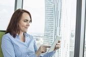 Mid-adult businesswoman using digital tablet in office