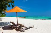 Chairs and orange umbrella on a beautiful tropical beach at Maldives