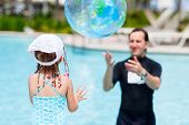 Adorable little girl and her father at swimming pool playing with ball