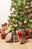 beautifully decorated christmas tree with a toy train and lots of presents