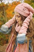 Cute casual woman dressed in pink knitted hat, scarf and gloves posing in autumn park.