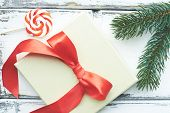 Composition of lollipop, conifer and xmas card with red silk bow