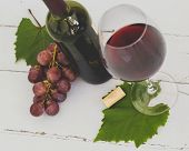 Glass of red wine with grapes on a wooden table