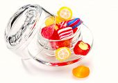 Multicolored sweets in a bowl of glass on white background