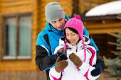 Half-length portrait of hugging couple who drinks tea outdoors during winter holidays
