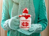Woman holding winter cup with nice Christmas toy close up on light background. Woman hands in woolen teal gloves holding a cozy mug with happy snowman toy. Winter and Christmas time concept.