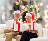 family, holidays, christmas, age and people concept - happy senior couple in santa helper hats with gift boxes over tree lights background