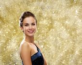 people, holidays, christmas, and glamour concept - smiling woman in evening dress over yellow lights background