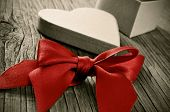 a red ribbon bow and a heart-shaped gift box on a weathered wooden table, with a retro effect