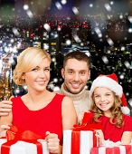christmas, holidays,  family and people concept - happy mother, father and little girl in santa helper hat with gift boxes over snowy night city background