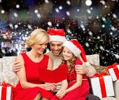 christmas, holidays,  family and people concept - happy mother, father and little girl in santa helper hats with gift boxes over snowy night city background