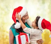 christmas, holidays, celebration, family and people concept - happy mother and child girl in santa helper hats with gift box over yellow lights background