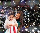 christmas, holidays, celebration, family and people concept - happy mother and little girl with gift box over snowy night city background