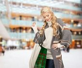 happiness, winter holidays, christmas and people concept - smiling young woman in winter clothes with bags over shopping center background