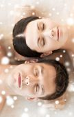 beauty, health, holidays, people and spa concept - happy couple with closed eyes lying in spa salon