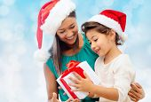 christmas, holidays, celebration, family and people concept - happy mother and little girl in santa helper hats with gift box over blue lights background