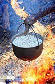 Tourist kettle with meat dumplings on hot fire