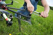 Closeup of young engineer tightening propeller of UAV drone with hand tool in park