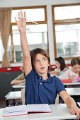 Portrait of cute schoolboy raising hand while studying at desk in classroom