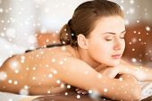 beauty, health, people and spa concept - beautiful woman in spa salon getting hot stones massage