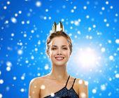 people, holidays, royalty and christmas concept - smiling woman in evening dress wearing golden crown over blue snowy background