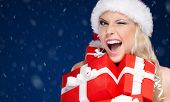Pretty woman in Christmas cap holds a set of presents, snowflakes background