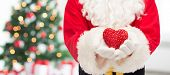 christmas, holidays, love, charity and people concept - close up of santa claus with heart shape decoration over living room with tree