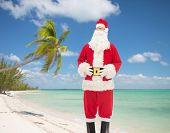christmas, holidays, travel and people concept - man in costume of santa claus over tropical beach background over tropical beach background
