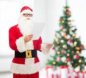 christmas, holidays and people concept - man in costume of santa claus reading letter over living room with tree background